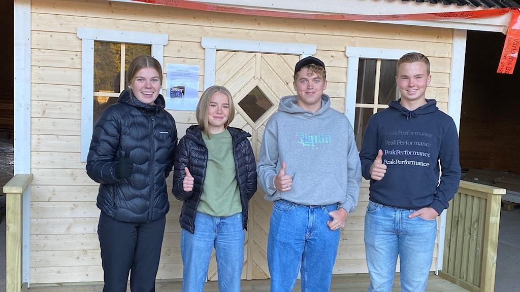 Fyra ungdomar står framför sin egenbyggda lekstuga.