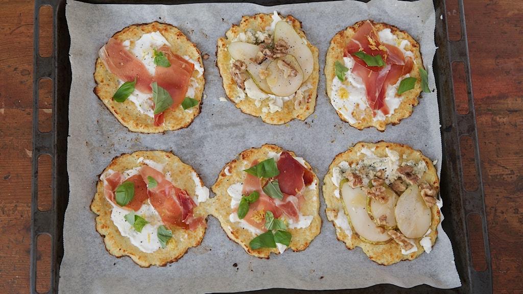 På en bakplåt ligger 6 stycken pizzor bakade med en botten gjord med blomkål.