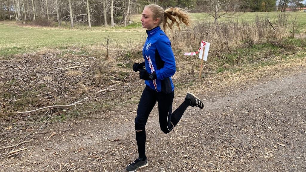 En kvinnlig löpare sträcker ut på steget.