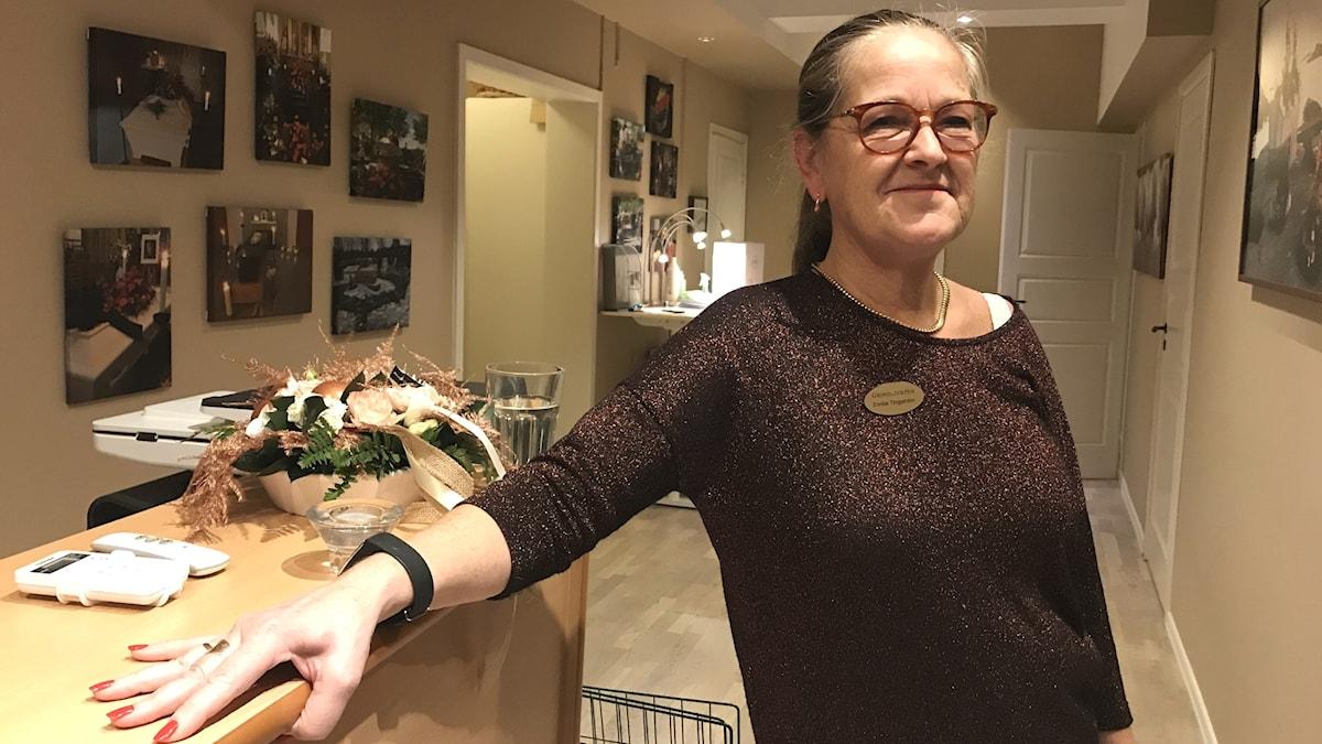 En kvinna står vid en skänk med sin arm som stöd.