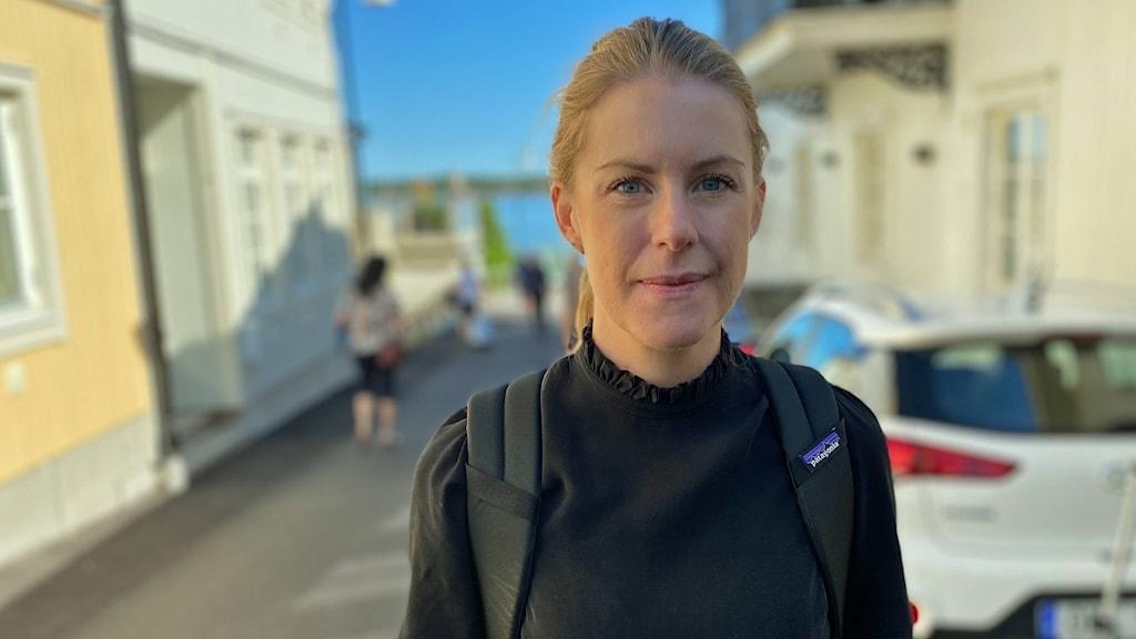 En kvinna står framför hus i Öregrund.