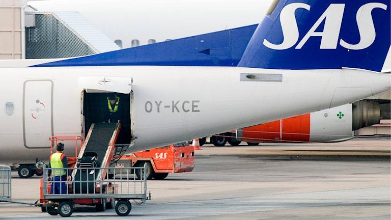 Markpersonal lastar ett SAS-plan. Foto: Bertil Ericson / Scanpix