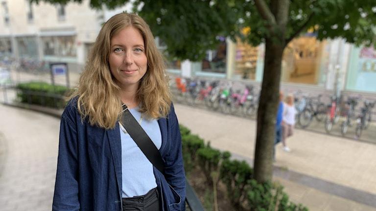 Lovia Sandström, en ung kvinna, står ute på en gågata.