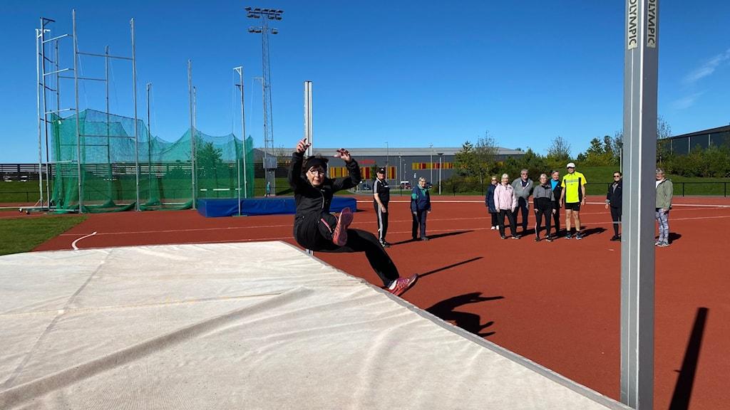 Barbro Gadle hoppar höjdhopp, några meter bakom står en grupp människor och tittar på.