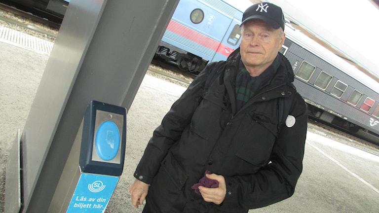 SL-stolpe och pendeltågsresenären Tom Sandstedt vid Uppsala resecentrum. Foto: Martin Hult/Sveriges Radio
