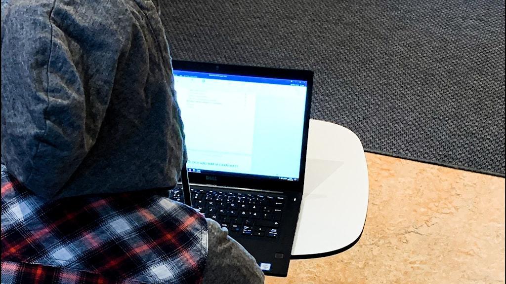 En person sitter med dator framför sig