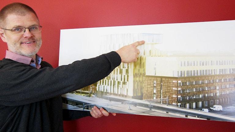 Henrik Lindley visar det nya niovåningshotellet som ska byggas. Foto: Julia Burman Görans/SR