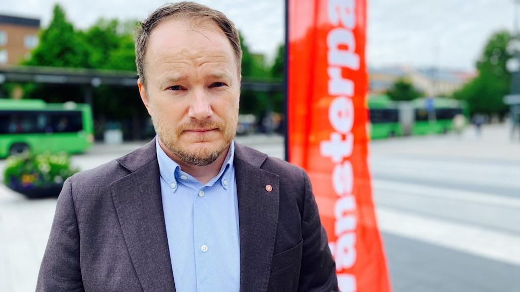En politiker framför Resecentrum i Uppsala.