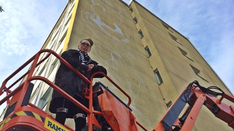 Carolina Falkholt painting a block of apartments. Photo: Henrik Skarstedt/SR.