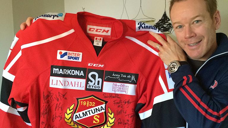 Almtunas tränare Niklas Eriksson med signerad tröja. Foto: Bosse Pettersson/Sveriges Radio