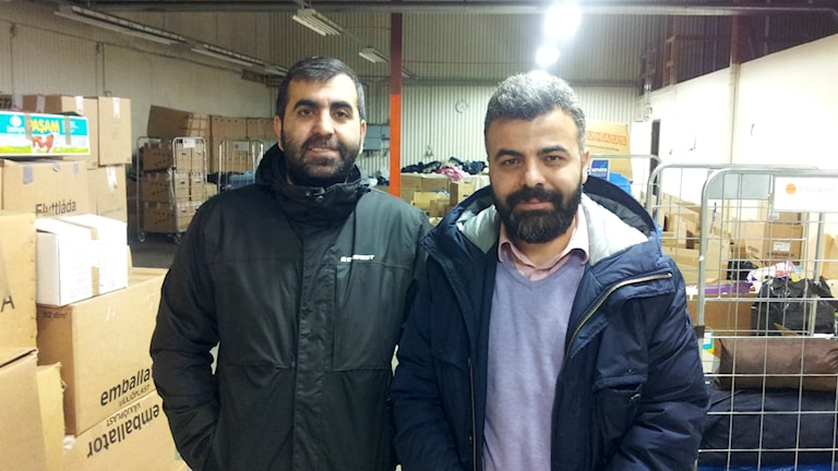 Hakan Yildiz och Emin Maskan bland väskor och kartonger med kläder och saker som skänkts. Foto: Christer Engqvist/SR
