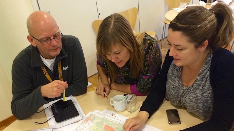 Sara Aron, informationschef, Mina Ashkan Far och Anders Leijeon krisberedskapshandläggare studerar kartan över det tänkta skogsbrandsområdet. Foto: Mattias Pleijel/Sveriges Radio