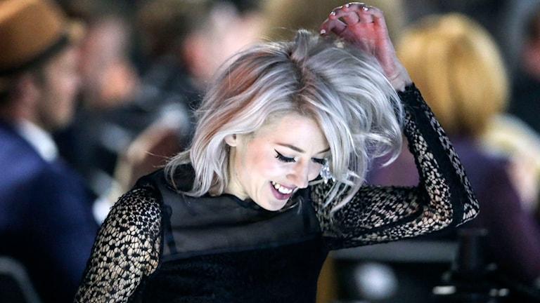 Veronica Maggio på väg upp på scenen för att ta emot P3 Guld-priset. Klädd i svart, pillar med fingrarna i håret. Foto: Björn Larsson Rosvall/TT