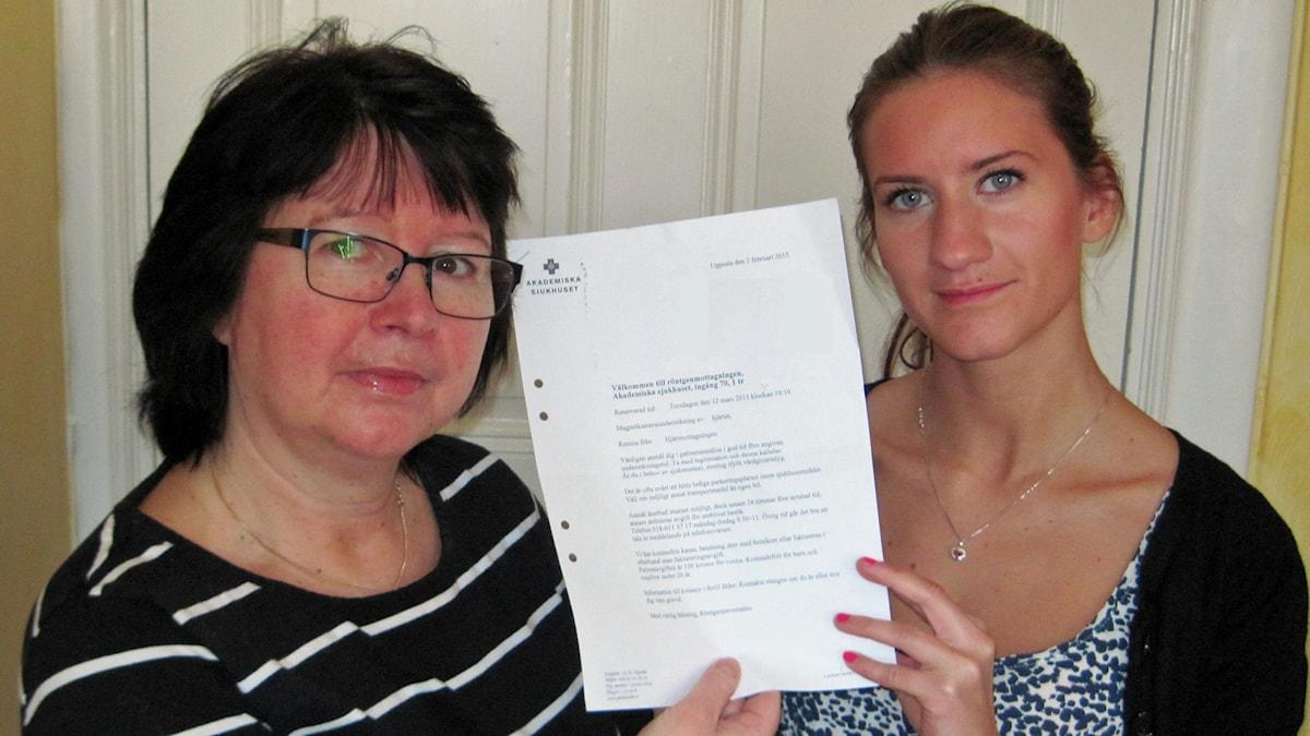 Hustrun Lottie och dottern Mathilda med kallelsen från Akademiska. Foto: Mårten Nilsson/Sveriges Radio