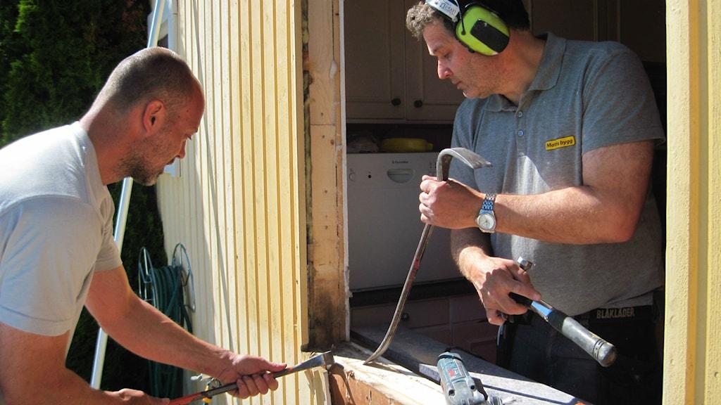Bildtext: Ariel Björfjell och Thomas Kruse är två av de hantverkare som har bråda tider just nu. Här lagar de ett fönster på en Uppsalavilla. Foto: Cinna Gärdenfors/SR.