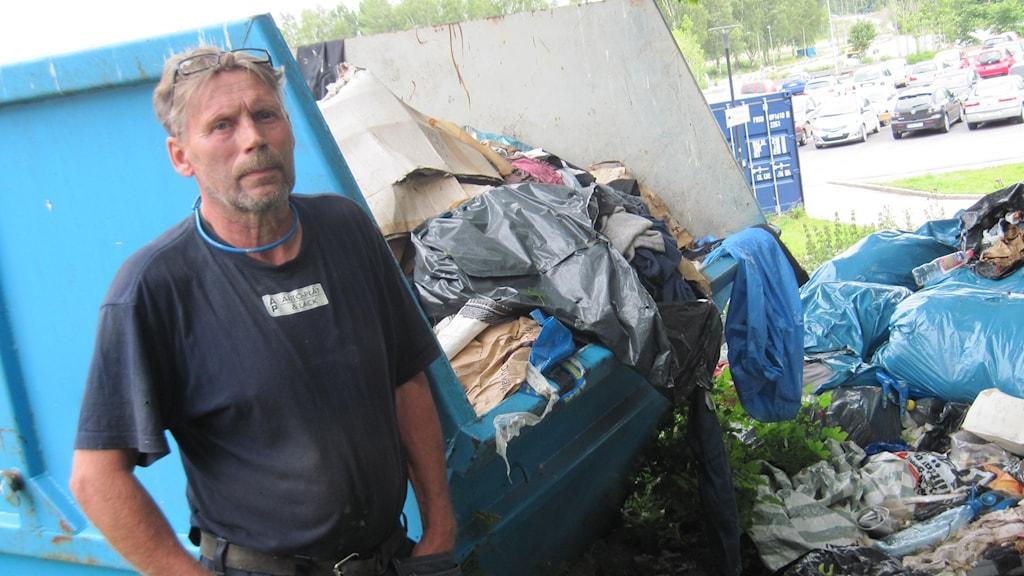 Runt containern har det blivit en soptipp, konstaterar Pekka Nyyssölä. Längst bort på parkeringen har ett läger för EU-migranter funnits. Foto: Mårten Nilsson/Sveriges Radio