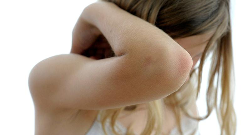 Armbågen på en flicka som håller upp armen som skydd för ansiktet Foto: Janerik Henriksson/SCANPIX