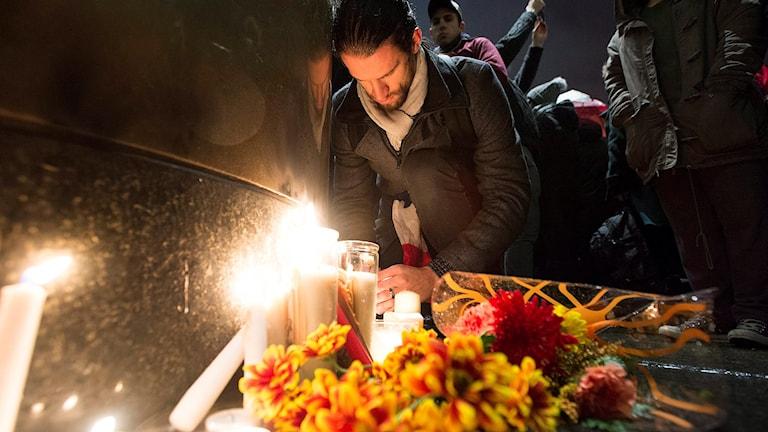 Människor tänder ljus vid franska konsulatet i Montreal. Foto Graham Hughes/AP)