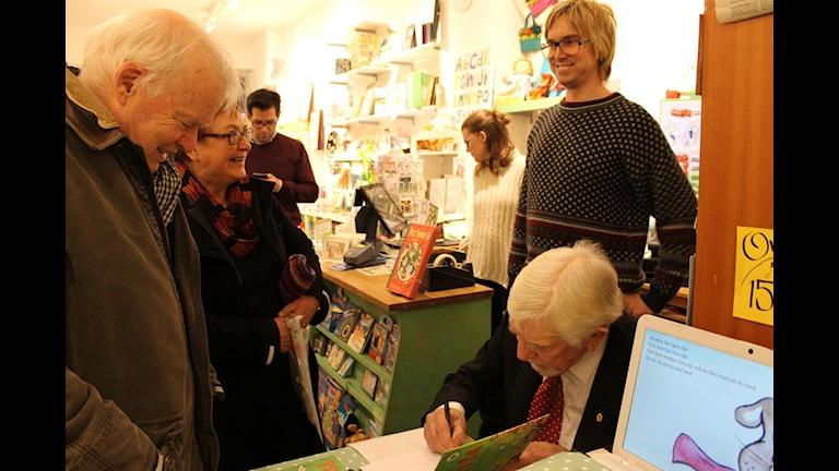 Owe Törnqvist signerar barnboken Titta Titta.  Foto Cinna Gärdenfors/Sveriges Radio