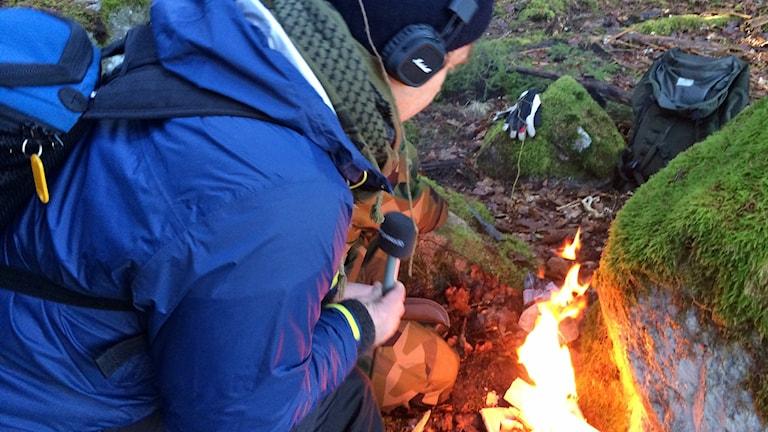 Bosse gör upp eld under Överlevnadsmåndag.
