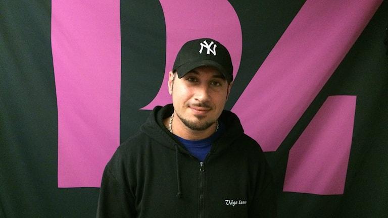 Vahid Rastegar, artist och programledare i Sveriges Radio, står vid en P4-logga.