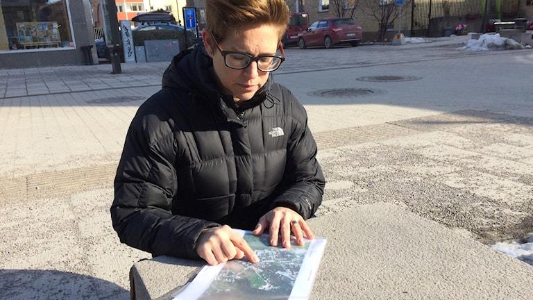 Tvåbarnsmamman Sanna Lafork visar på en karta var det riskabla övergångsstället är. Foto: Jonas Ahlman/Sveriges Radio.