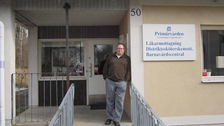 Ola Dahlbäck utanför den vårdcentral han inte längre är välkommen till, trots ortsbefolkningens stöd.