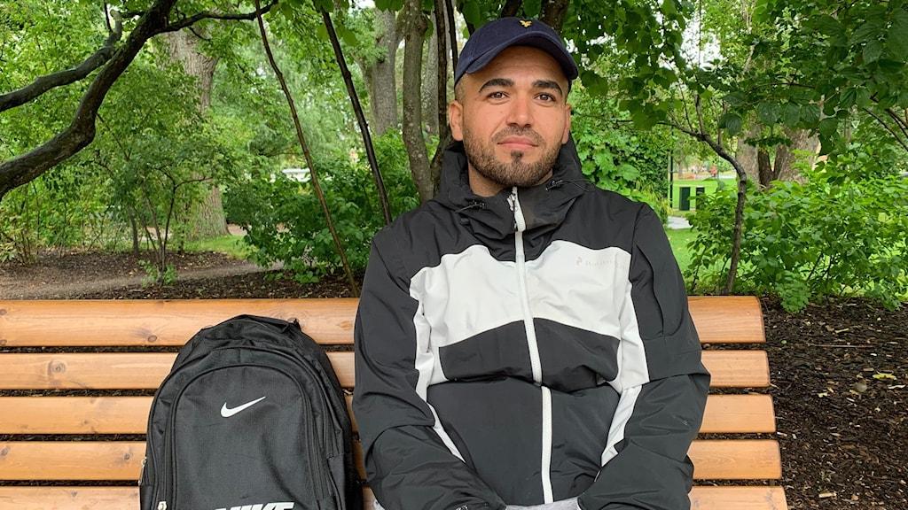 Praktikanten Raed Almassri sitter på en parkbänk.