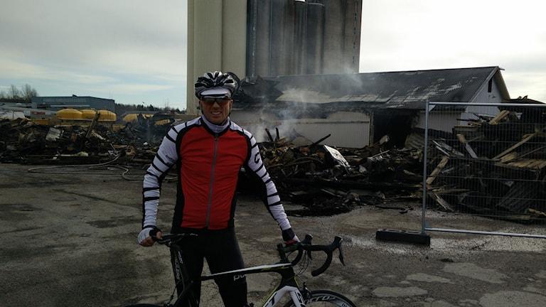 Cyklist framför den nerbrunna affären