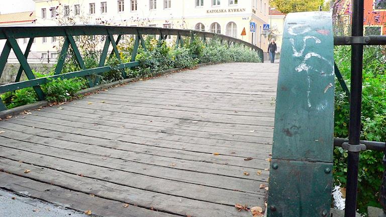 Träbro med gröna räcken.