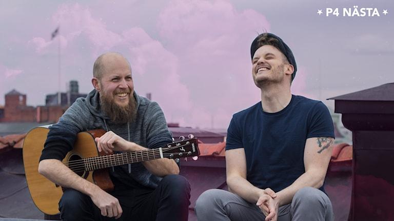 Två skrattande män sitter på ett tak, en håller i en gitarr.