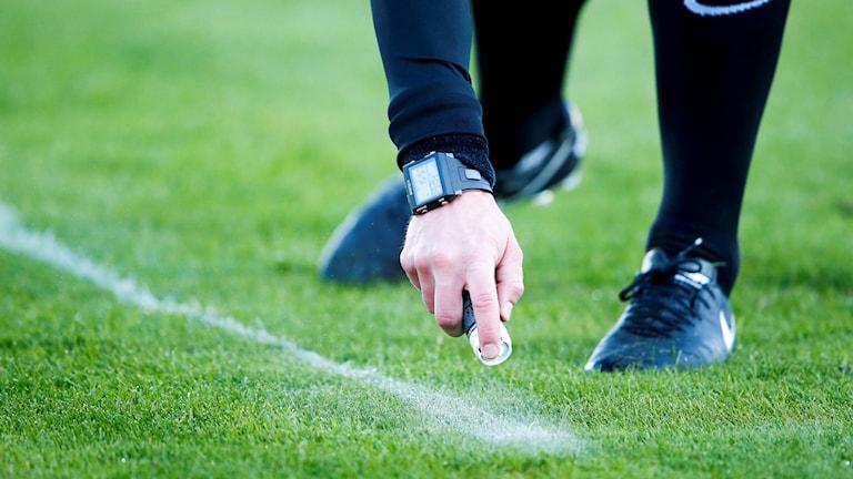 En fotbollsdomare sprejar linjer på planen.