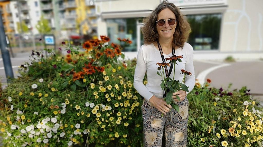 Ann-Katrin Thor på Knivsta kommun bland blommor som ska skänkas bort.