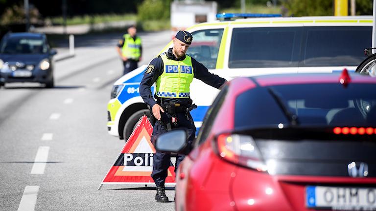 Polis vinkar åt en bil att köra in mot vägkanten.