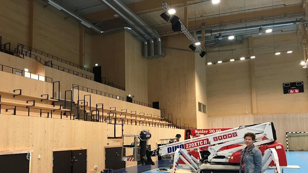 I idrottshallen på CIK står stora maskiner som ska förstärka taket. På bilden syns även Catrine Wermelin, fritidschef i Knivsta kommun.