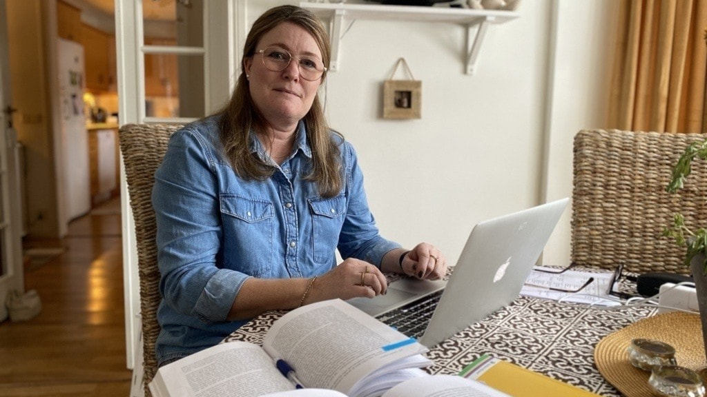 En kvinna med glasögon och blå skjorta som sitter vid ett bord framför en dator och fler böcker.