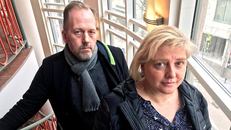 En pappa och en mamma står i en trapp.