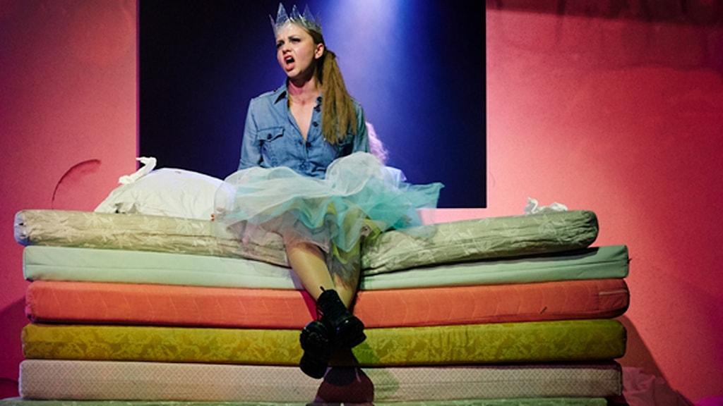 Skådespelerskan Anna Åström har i dansteaterkonserten Eka över hela staden på Uppsala stadsteater. Hon har en papperskrona på huvudet och sitter på en hög med madrasser i olika färger och sjunger.