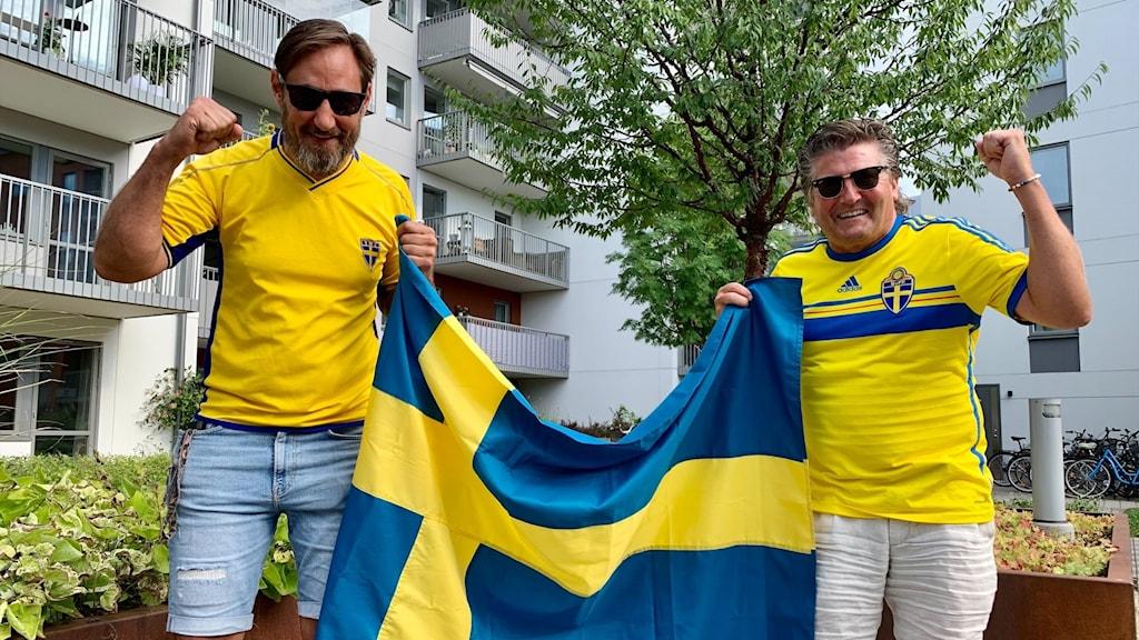 Två män i fotbollströjor håller upp en svensk flagga och höjer nävarna i luften i en segergest.