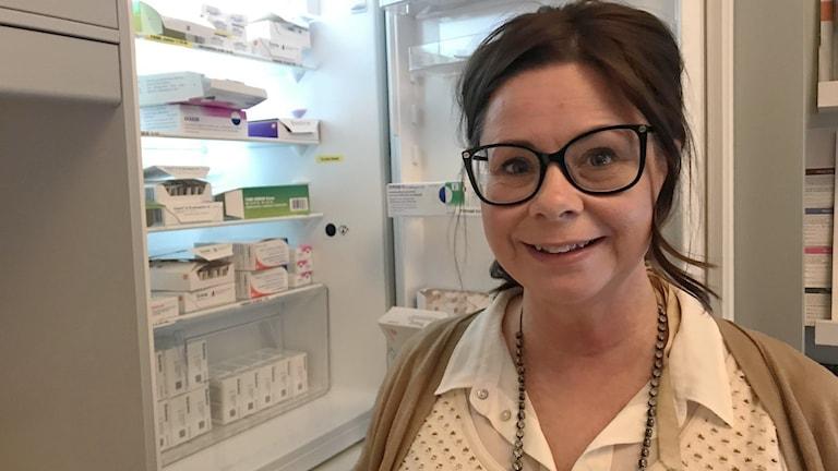 Kvinna framför öppet kylskåp fullt med vaccin.