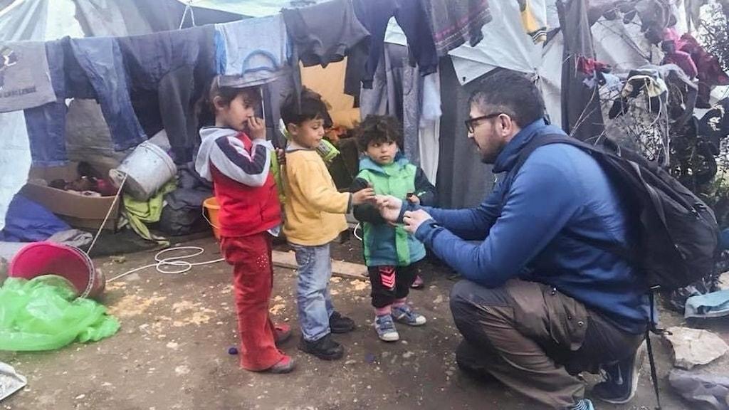 En man med mörk hår och glasögon och en mörkblå tröja pratar med tre små barn. I bakgrunden syns tält i ett flyktingläger.