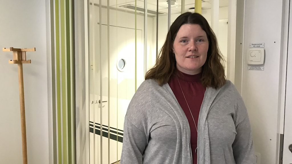 Monica Eriksson på Länsstyrelsen i Uppsala står i ett vitt rum. Bakom sig har hon en fönsterruta som vetter mot korridoren utanför.