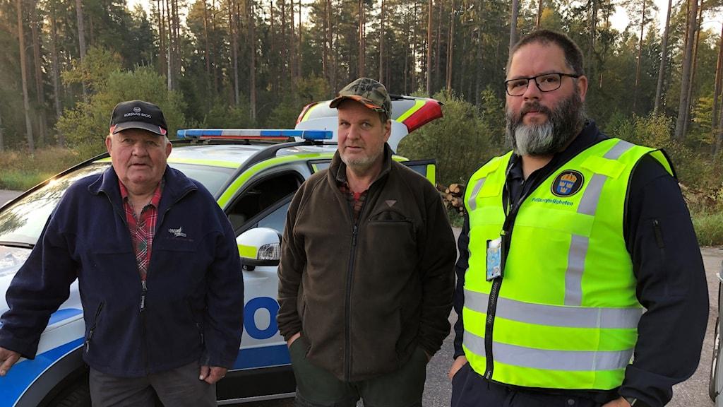 Tre män, två jägare och en polis, står framför en polisbil.