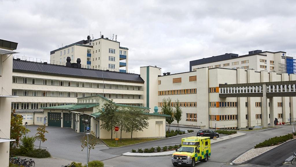 Byggnad, ambulans är parkerad framför.