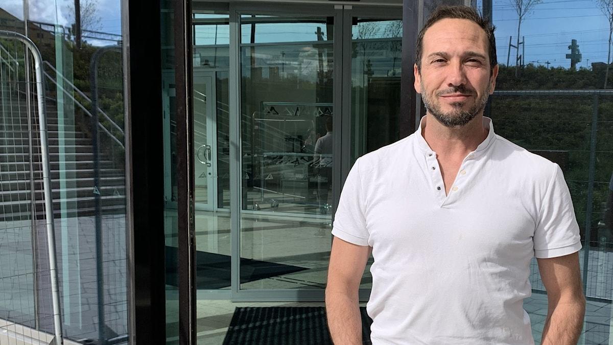 En man med mörkt hår och ljus tröja står framför en glasbyggnad.