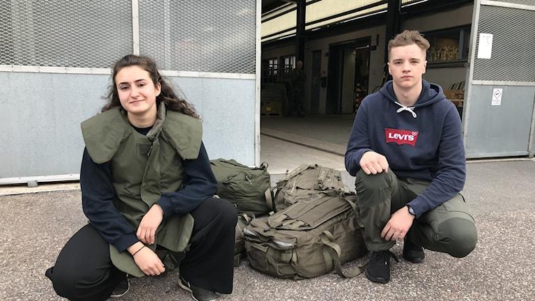 En tjej och en kille sitter på huk utanför en garnisonsbyggnad.