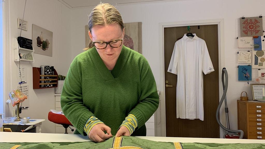 Victoria Wik står böjd över arbetsbord med tyg på.