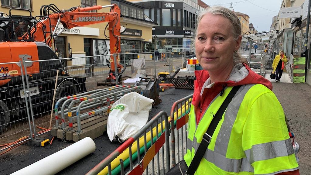 Kvinna står vid byggarbetsplats i centrala Uppsala.