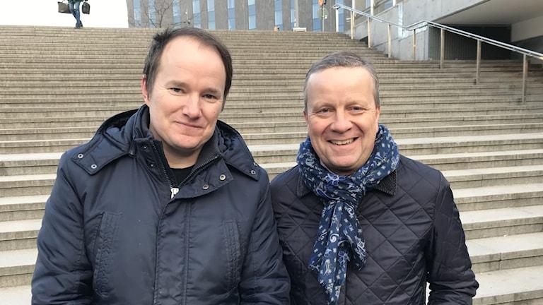 Till vänster en man med brunt hår och mörkblå jacka. Till höger en man med blont hår och svart jacka med blå halsduk.