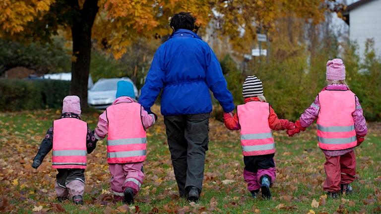 Förskolebarn går hand i hand med förskolelärare i mitten.